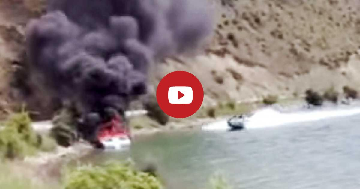 A Boat Lies Just Offshore Smoldering In Flames And Dark Black Smoke But The Speedboat But Miraculously Helps Put Out Fire.