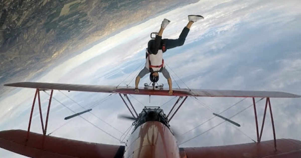 Daredevil With A Death-wish Dangles From The Wing Of An Upside-down Plane Before Letting Go.