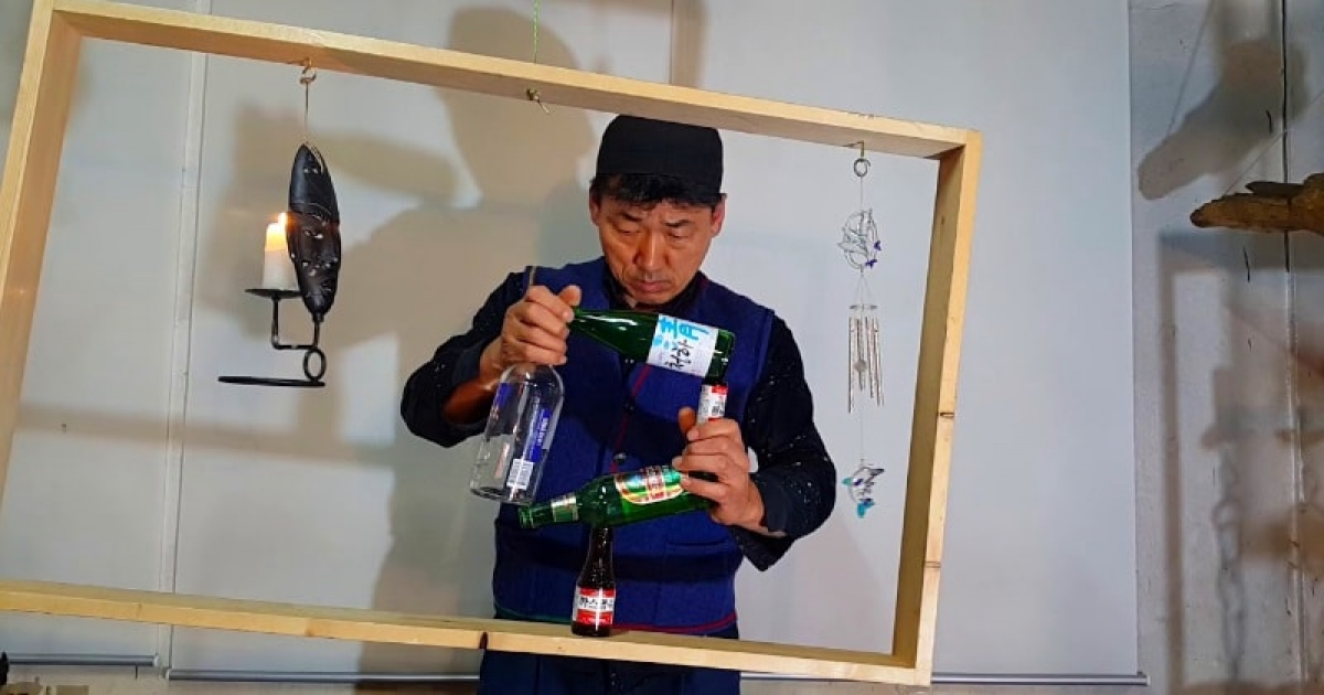 This Unique Balancing Artist Stack Bottles Inside An Swing Wooden Frame.