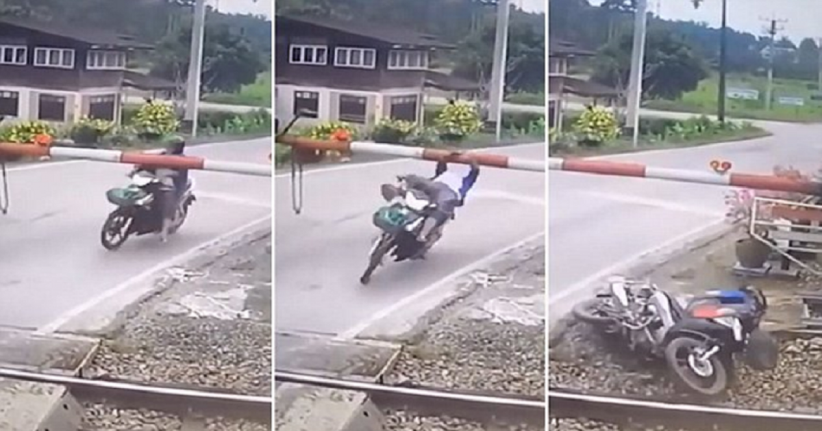 Female Motorcyclist Is Sent Flying After Smashing Into Level Crossing Barrier And Narrowly Misses Being Killed By Oncoming Train.