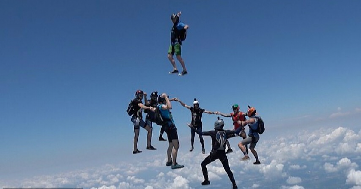 A Group Of Fearless Skydivers Plummet Head First Towards The Ground During Epic Mid-air Trick-shot.