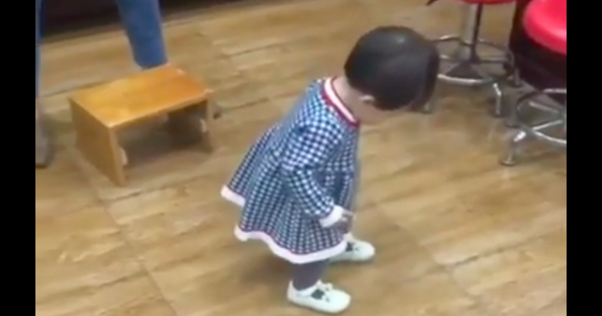 Adorable Little Girl Tries To Move Backward And Sit On A Chair.
